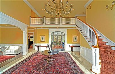 Grand entry way features elegant chandelier and custom millwork.