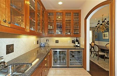 Butler's pantry features dual wine refrigerators and sink. It connects with formal dining room on right.